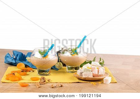 A beautiful composition of two dessert glasses filled with thick cocktail isolated on a white background. Smoothie with decorative mint leaves, physalis and bright blue straws on a light wooden table.
