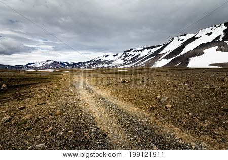 Dramatic scenery of icelandic dirt road towards mountains of Porisdalur. Moody sky above Kaldidalur area in the Highland of Iceland.
