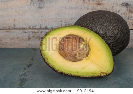 Fresh avocado sliced over vintage background close up. Ripe green avocado fruit on cement board
