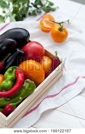 Fresh vegetables, tomatoes, peppers, aubergines, chilli pepper in a wooden box in the open air. Vegetable background.
