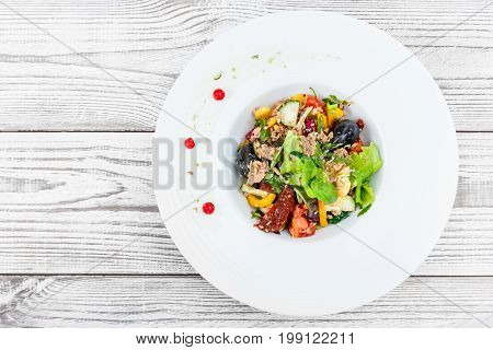 Fresh salad with tuna arugula artichokes codfish olives basil sun dried tomatoes cherry tomatoes cucumber cauliflower on wooden background close up. Mediterranean food. Top view