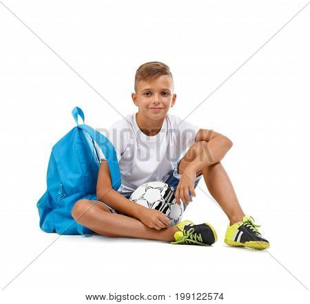 Happy little boy isolated on a white background. A smiling kid with a ball and a blue satchel sitting on the ground in a lotus pose. Lucky schooler with a soccer ball. School concept.