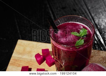 A spacious glass of fantastic thick red juice on a lighted wooden background. Beetroot smoothie with decorative mint leaves. Dark pink beet cut in cubes for a nutritious salad. Refreshing beverages.
