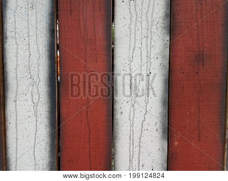 red and white fence with black streaks or drips