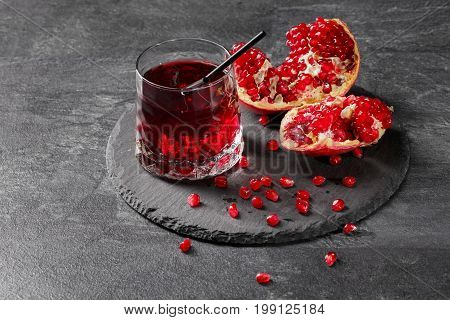 A transparent glass full of sweet pomegranate juice and a cut garnet on a round plate on a dark gray background. Summer, healthful and fruity red cocktail with black straw and fresh garnet.