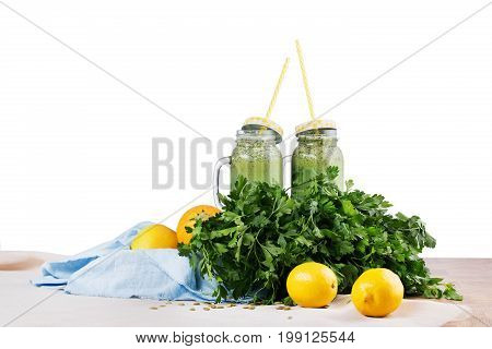 Two mason jars full of green smoothies on a blue fabric, isolated on a white background. Cocktails from celery, parsley, spinach, and cucumber. Lemons, yellow zucchinis, branches parsley on a desk.