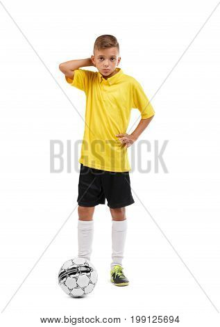 Full-length photo of an adorable teenager wearing a yellow football uniform, isolated on a white background. A non-confident boy scratches his head. Sport, football and healthful concept.