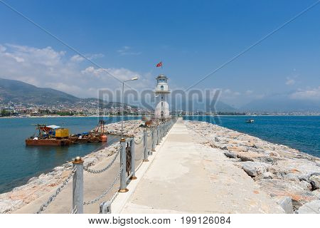 ALANYA TURKEY - JULY 09 2015: The lighthouse and long pier at the entrance to the sea port of Alanya. Alanya - a popular holiday destination for European tourists.