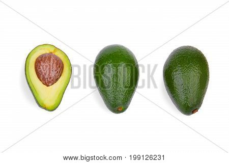 A top view of two whole green avocados and one cut in half, isolated on a white background. An organic, fresh, and ripe avocado with a large stone. Three healthful and colorful fruits in a row.