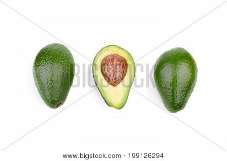 A top view of two whole green avocados and one cut in half in a center, isolated on a white background. A fresh, natural and ripe avocado with a large stone. Three healthful fruits in a row.