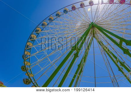 Large multicolored ferris wheel with blue sy background