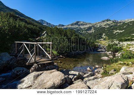 Wooden bridge over Mountain river and Banderishki Chukar peak, Pirin Mountain, Bulgaria