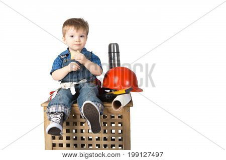 Little funny builder boy eating cookie in rest on white background.