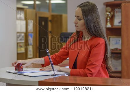 Young Woman Secretary In Office-stamps To Documents