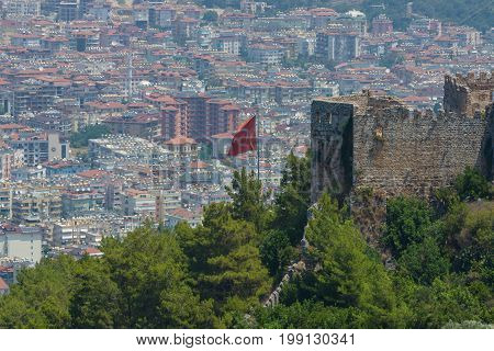 Turkish flag on the background of houses of the central district of Alanya. View from the ancient fortress of Alanya.