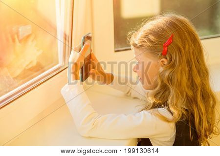 Covered image of a charming little girl with her blond hair relaxing near the window using wi-fi on a mobile phone in a green case enjoying an online connection after school hours