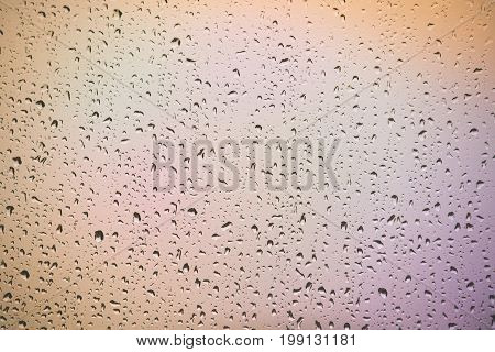 Raindrops on the home window surface against colorful pinkish background