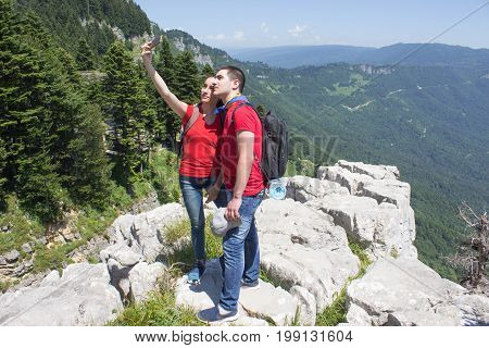 Eco tourism and healthy lifestyle concept. Young hiker girl end boy with backpack. Active hikers. Tours on the viewing platform In the mountains reserve