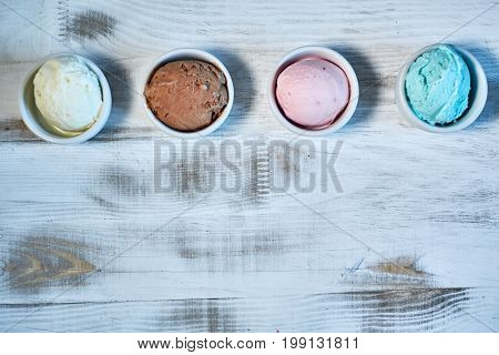 Selection of gourmet flavours of Italian ice cream in vibrant colors served in individual porcelain cups on an old rustic wooden table in an ice cream parlor, angle view
