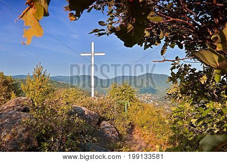 Big Christian cross on the way to Mlynaruv kamen lookout to valley of european river Labe in Czech central mountains tourist area in sommer sunset