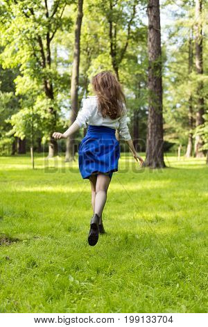 girl with long hair in blue skirt runs back across the meadow with green grass among the trees