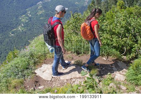 Two young Tourists With Backpacks travel. Active hikers. Two young Tourists With Backpacks travel