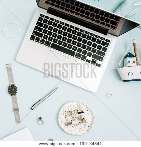Top view flat lay home office desk. Women workspace with laptop white peony flowers bouquet accessories on blue background.