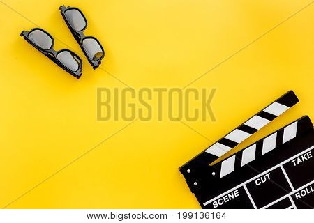 Filmmaker accessories. Clapperboard and glasses on yellow background top view.