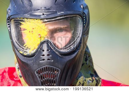 Portrait of a man with splash on helmet after direct hit in the paintball game