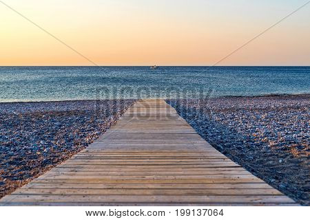 morning sea landscape of the empty beach with a path from a wooden flooring closeup and sharpness on a background