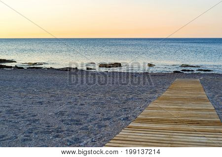 sea landscape of the empty beach with a path from a wooden flooring closeup with sharp prospect
