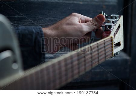 Caucasian male hand tuning an acoustic guitar on black dark wooden background with selective focus