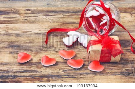 Marmalade candy shape heart in glass jar with red ribbon gift box for Valentine's Day on wooden table closeup