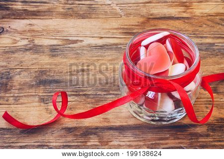 Jelly candy shape heart in glass jar with ribbon for Valentine's Day closeup