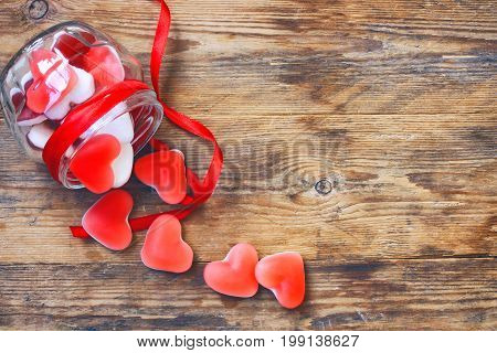 Marmalade candy shape heart in glass jar with ribbon gift for Valentine's Day top view space for text