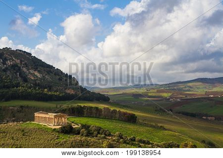 Dramatic landscape and ancient greek doric temple in Segesta archaeological area, Sicily, Italy.