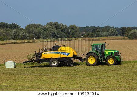 ACHTERHOEK THE NETHERLANDS - SEP 4 2012: John Deere 6930 tractor and New Holland BB9060 CropCutter hay baler at work.