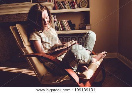 Spending free time by reading books. Home and comfort concept. Woman smiling reads interesting book in comfortable modern chair. Natural light. Enjoy moment. Warm atmosphere. Knowledge, learn concept.