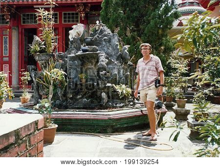 SINGAPORE / CIRCA 1990: An American tourist poses for a photograph in the courtyard of the Kwan Im Thong Hood Cho Temple.