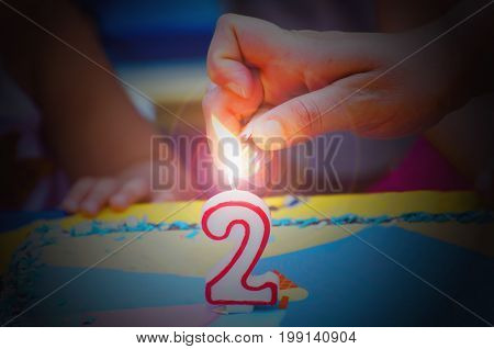 Hand With A Lighter About To Fire A Two Years Birthday Candle.jpg