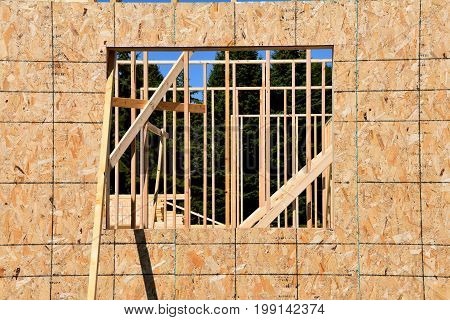 A building under construction has a window space cut in a a sheet of plywood.