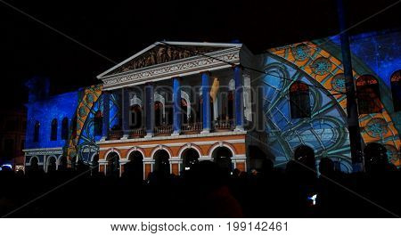 Quito, Pichincha / Ecuador - August 9 2017: Crowd admiring the spectacle of lights projected on the facade of the Teatro Sucre, in the historical center of Quito. Fiesta de la Luz is an event that takes place in Quito every August