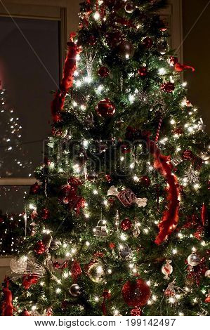 Evening shot of Christmas tree with red and sliver ornaments and white lights