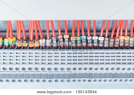 Lot electrical feedthrough terminals arranged in a row. To them are attached the electric wires marked. Marking with numbers. Marking of a different color. The wires go into the cable channel.