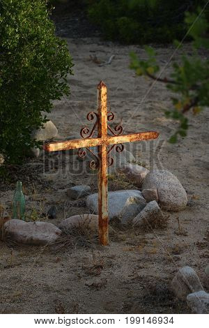 Sunlit metal cross on an old grave in remote Baja Sur, Mexico in sand and rocks.