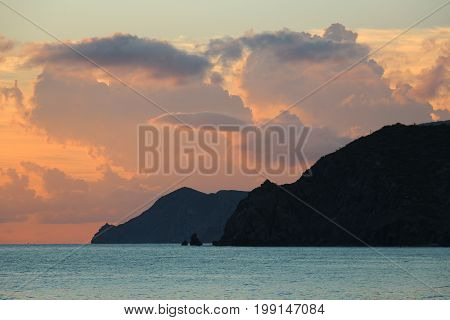 Pink evening sky with clouds, black cliffs and turquoise blue sea after sunset in Baja Sur, Mexico