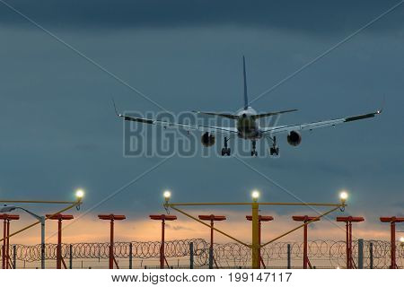Plane landing on the airport at the sunset time