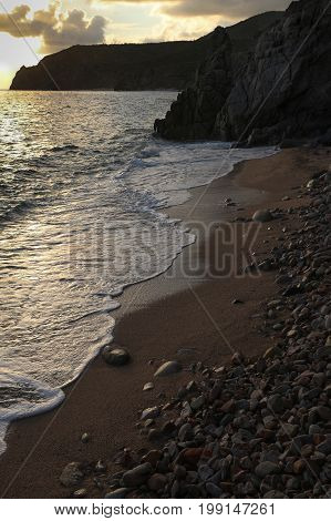 Late evening rugged Mexican sandy beach with dark cliffs, sea, rocks and reflections.