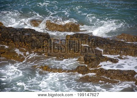 Photo of several rocks with sea and sunlight