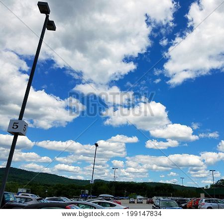Blue sky, puffy white clouds, dramatic flood lights over a parking lot